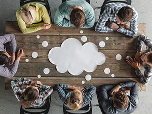 Image of people around a table with a thought bubble in the middle